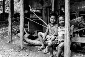 Two boys sitting on edge of eaves