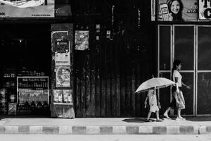 Little girl putting big umbrella up