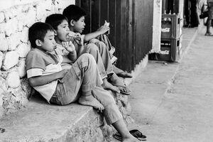 Three boys sitting by the wayside