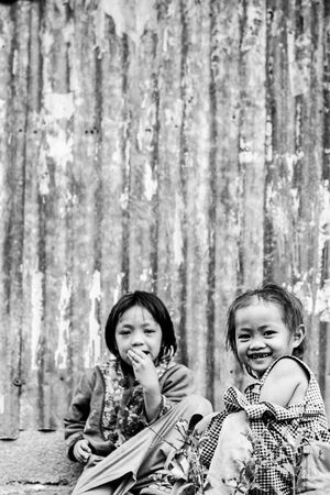 Two girls sitting in front of corrugated wall