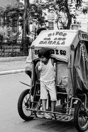 Boy getting on back of tricycle
