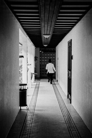 Hotel employee running corridor