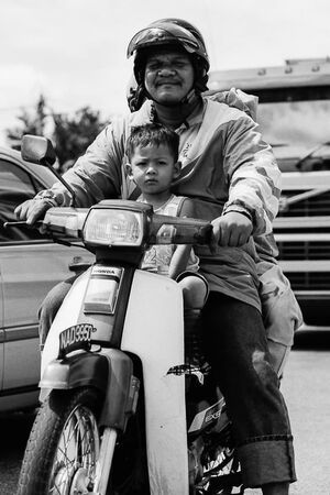 Father and son riding on same motorbike