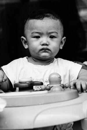 気難しそうな顔をした歩行器の赤ちゃん
