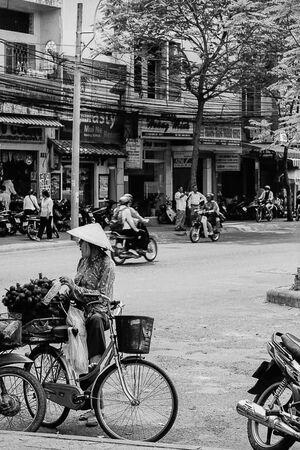 道端に自転車を停めた女性の行商人