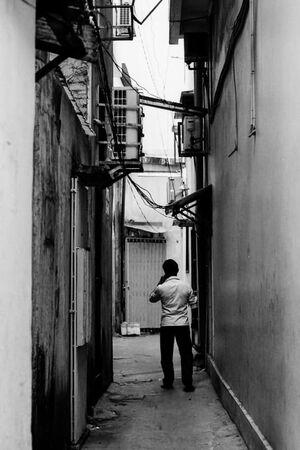 Man standing in dim lane