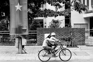 Bicycle passing by national flag