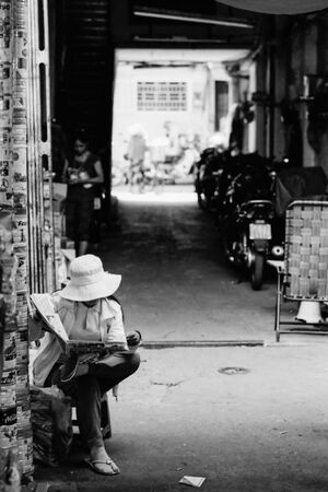 Hatted woman reading newspaper