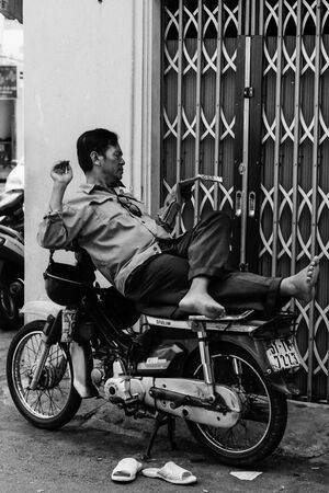 Man reading magazine on motorbike