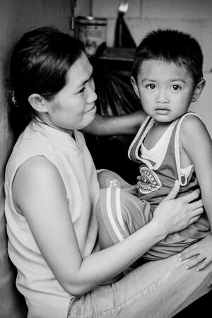 Boy sitting on mother's knees