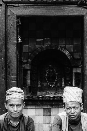 Two men sitting in front of small shrine