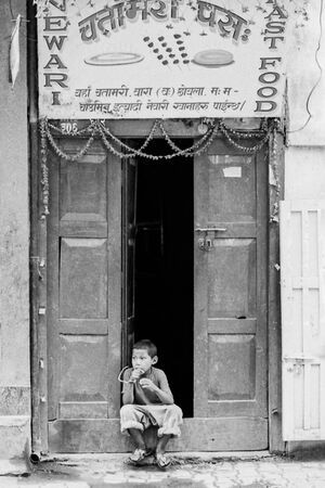Boy sitting in front of restaurant
