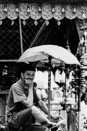 傘に下で客待ちするリクシャワラー