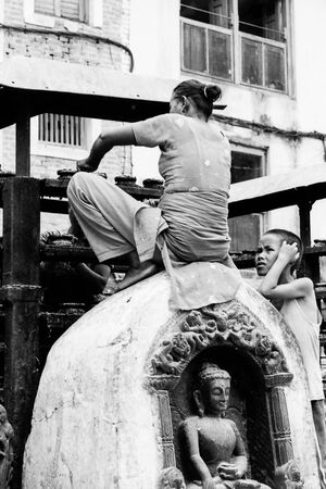 Woman sweeping while sitting on statue of Buddha