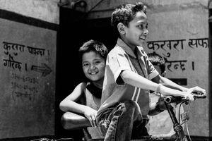 Boys playing around bicycle