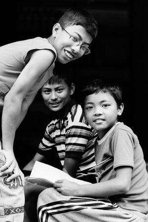 道端で一緒に宿題をする男の子たち