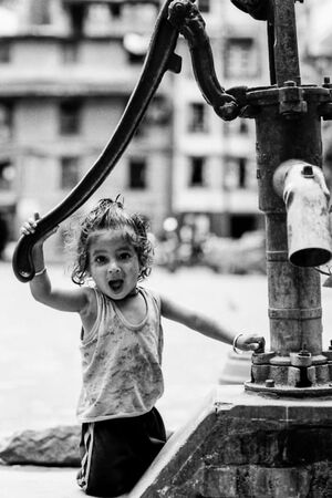 Girl opening mouth wide beside a well