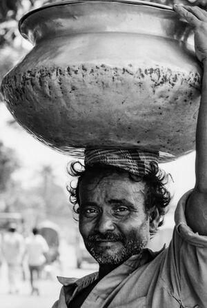 Man carrying jar on head