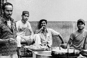 Four men around pans