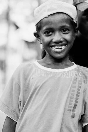 可愛らしく笑うイスラム帽をかぶった男の子