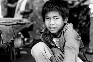 Boy squatting by wayside