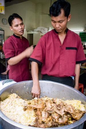 Man scooping Biryani