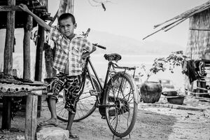 Boy posing in front of a bicycle