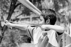 パチンコのゴムを引く男の子