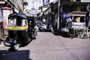 Auto rickshaw running street corner