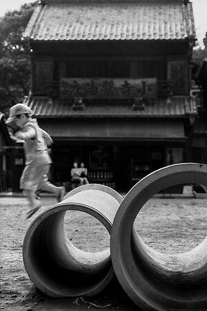 土管の上で遊ぶ男の子