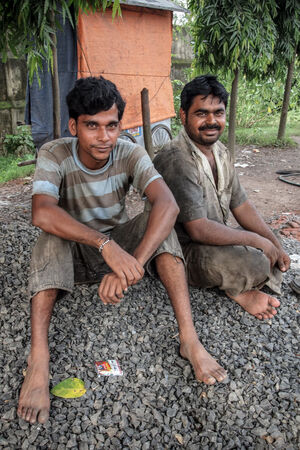 Men sitting on gravel