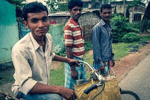 ベルハンポルの田舎道を歩く三人の男たち