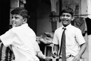歩道でクリケットをする男の子たち
