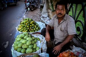 Man selling mango and pomegranate on the side of the road