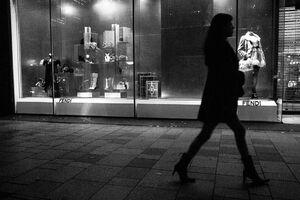 ショーウインドウの前を歩くハイヒールの女