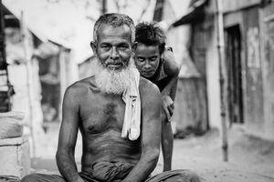 Boy standing behind old man