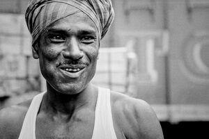 笑う頭に布を巻いた労働者