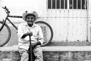 道端に腰を下ろしたカウボーイハットを被った老人