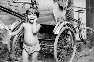 Little girl beside cycle rickshaw