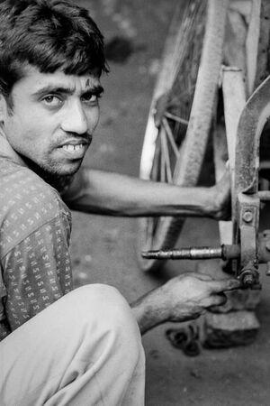 Man repairing cycle rickshaw