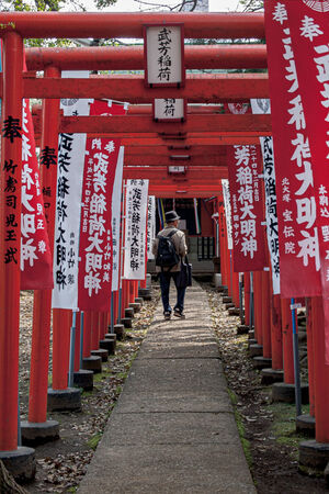 Old man passing through Torii