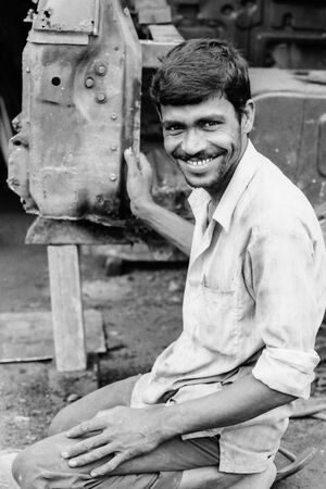 Man smiling beside car body