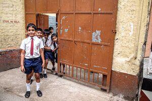 校門の前に立つネクタイを締めた小学生
