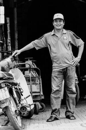 バイクの横で微笑む男