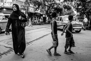 Muslim woman and boys crossing street