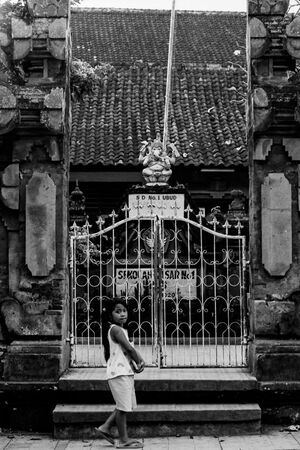 Girl walking in front of gate of school