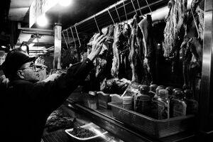 お肉屋さんで手を伸ばす男