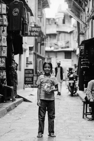 路地の真ん中に立ち止まった笑顔の女の子