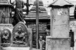 Boy playing among Buddha images
