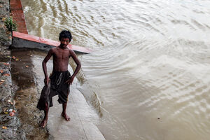 Young man standing on edge of water of Hooghly river